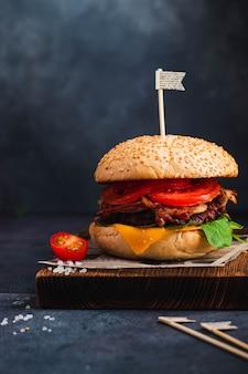 Frischer leckerer rindfleischburger auf holzschneidebrett gebraten