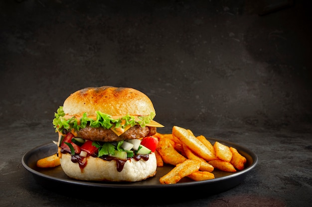 Frischer leckerer schweinefleischburger mit pommes frites auf dunklem hintergrund