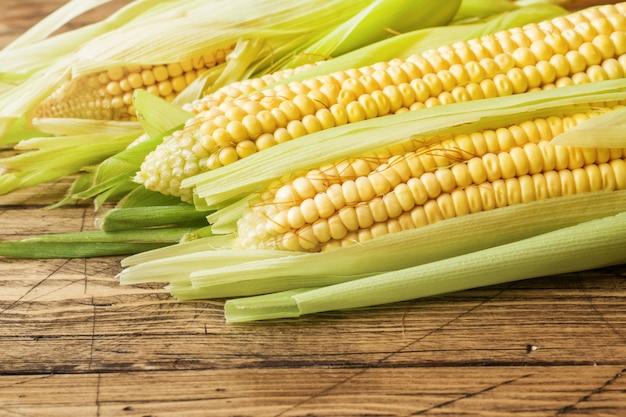 Frischer mais auf maiskolben auf rustikalem holztisch, nahaufnahme