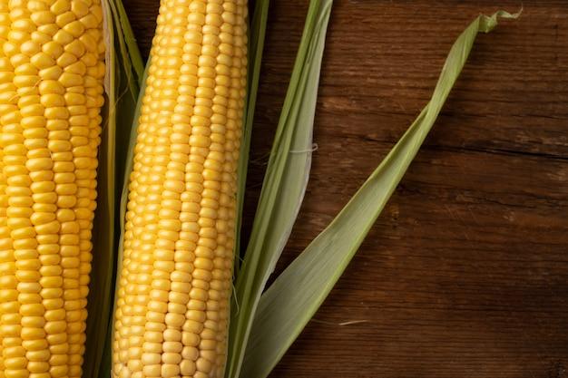 Frischer mais auf maiskolben auf rustikalem holztisch.