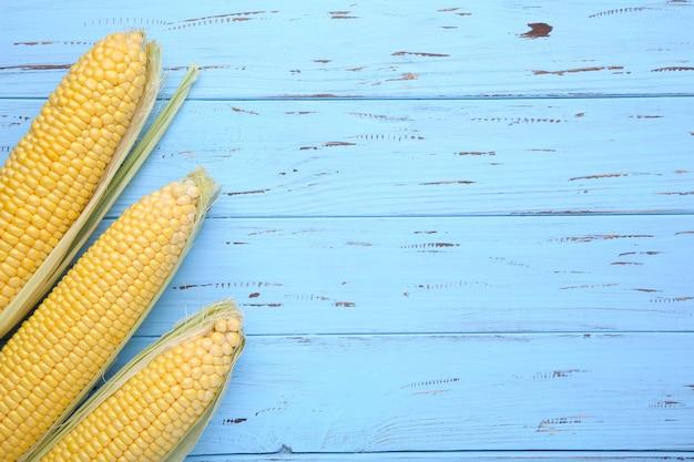 Frischer mais auf pfeilern auf einem blauen holztisch, nahaufnahme