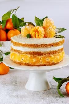 Frischer mandarinen-biskuitkuchen, dekoriert mit ganzen mandarinen.