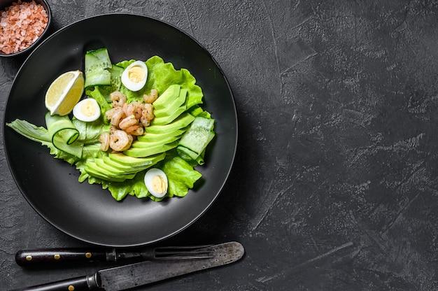 Frischer meeresfrüchtesalat mit gegrillten garnelengarnelen, ei, avocado und gurke in einem teller.