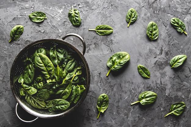 Frischer minispinat in einem sieb auf dem alten betontisch. gesundes essen, öko-produkt. vegan