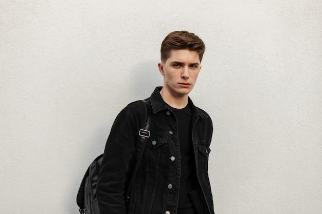 Frischer, modischer junger mann mit trendiger frisur in stilvoller schwarzer jeansjacke mit lederrucksack in der nähe des vintage-gebäudes in der stadt. attraktiver amerikanischer typ des models entspannt sich auf der straße.
