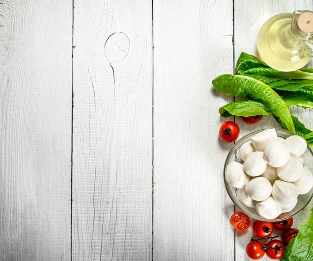 Frischer mozzarella mit olivenöl, tomaten und kräutern auf einem weißen hölzernen hintergrund