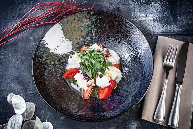 Frischer mozzarella-salat mit tomate, gewürzt mit salbei-pesto und weißer sauce. draufsicht, flach gelegtes essen mit kopierraum. italienische küche. gesundes essen, diät, vegan. schüssel salat. gewürztes essen