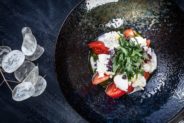 Frischer mozzarella-salat mit tomate, gewürzt mit salbei-pesto und weißer sauce