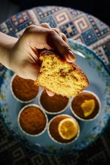 Frischer muffin in der hand einer frau. nahaufnahme textur des teigs.
