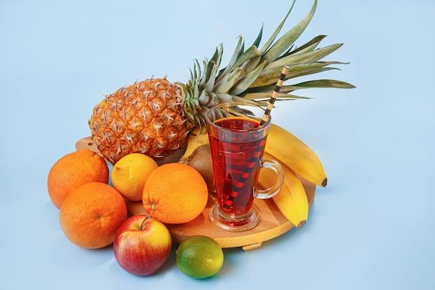 Frischer multifruitsaft mit eis in einem glas. ananas, orange, banane, zitrone, apfel auf einem blauen raum