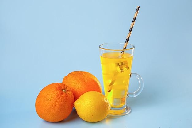 Frischer multifruitsaft mit eis in einem glas. orange und zitrone auf einem blauen raum