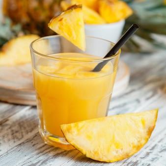 Frischer natürlicher ananassaftcocktail oder frischer ananassaft auf weißem holztisch. leckerer saft im glas mit zutaten ananasscheibe. quadrat. hochwertiges archivfoto