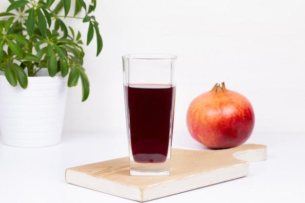 Frischer natürlicher organischer roter granatapfelsaft in einem glas auf einem brett, grüne blume in einem topf, lokalisierter weißer hintergrund.