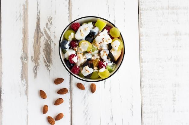 Frischer obstsalat mit joghurt und mandeln in einer schüssel auf einem weißen holztisch. gesundes essen. ansicht von oben.