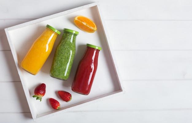 Frischer orange, erdbeere und brokkoli smoothie in den flaschen mit früchten und minze in einer weißen hölzernen rustikalen box