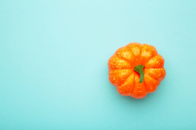 Frischer orange kürbis auf blauem pastellhintergrund