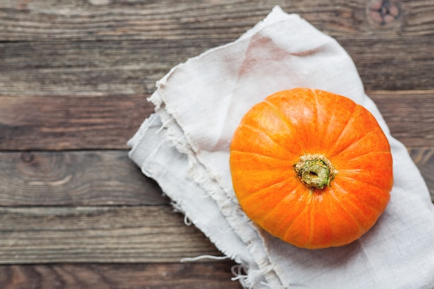 Frischer orange kürbis auf selbstgesponnener serviette