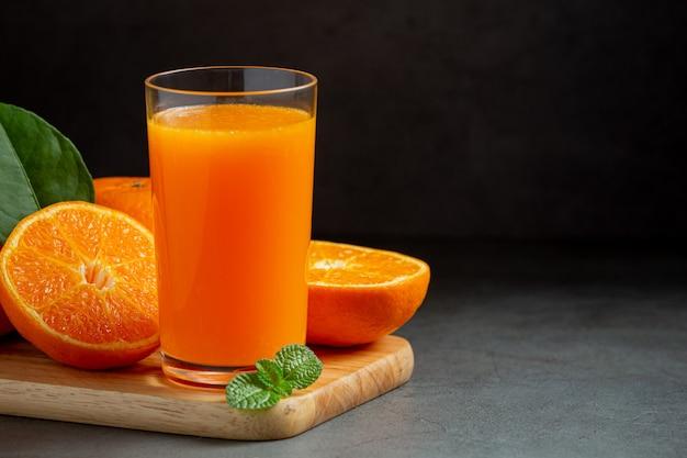 Frischer orangensaft im glas auf dunklem hintergrund