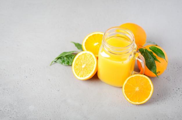 Frischer orangensaft in einem glas auf grauem beton.