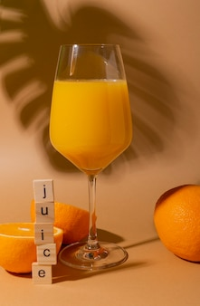 Frischer orangensaft mit fruchtfleisch in einem weinglas auf beige