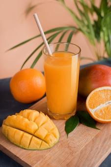 Frischer orangensaft mit reifer mango und orangenfrucht auf holzbrett wooden
