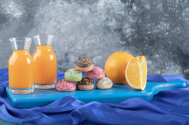Frischer orangensaft und obst mit hausgemachten keksen auf blauem holzbrett.