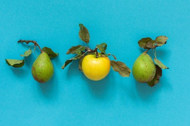 Frischer organischer gelber apfel und grüne birnen mit blättern in der mitte auf blauem hintergrund