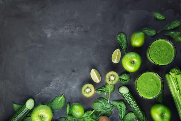 Frischer organischer grüner smoothie mit bestandteilen auf grauem betonhintergrund. draufsicht. speicherplatz kopieren.