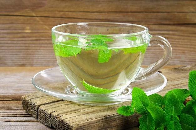 Frischer organischer tadelloser tee im glas auf holztisch.