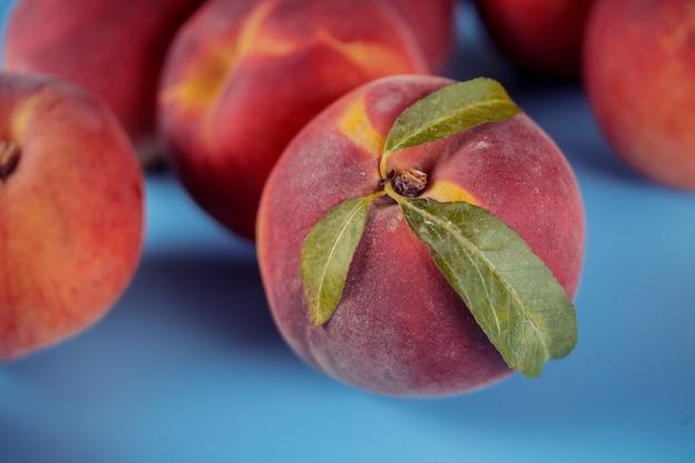 Frischer pfirsich whit verlässt auf blauem hintergrund