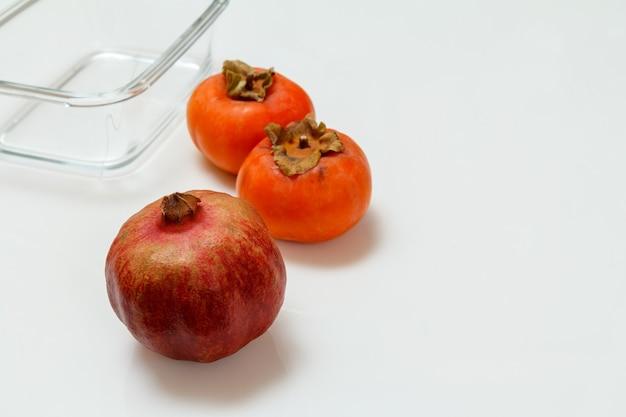 Frischer reifer granatapfel, kakifrüchte und eine glasschüssel auf dem weißen hintergrund. bio-früchte.