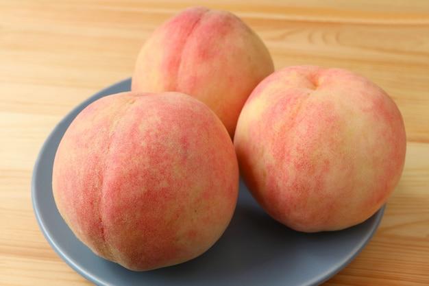 Frischer reifer pfirsich drei auf der blauen keramischen platte gedient auf holztisch.