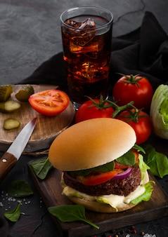 Frischer rindfleischburger mit soße und gemüse und glas cola-erfrischungsgetränk mit kartoffelchips-pommes auf steinküche.