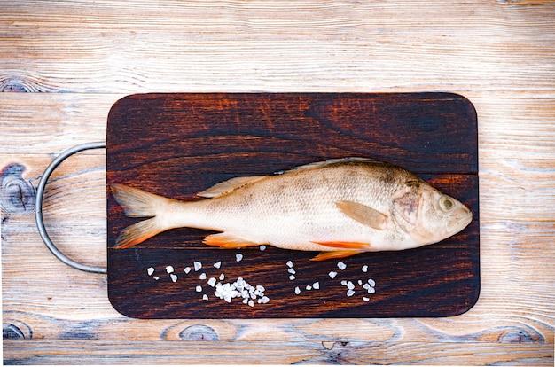 Frischer roher fisch auf einem dunklen hölzernen hintergrund. flussbarsch und gewürze. minimalismus