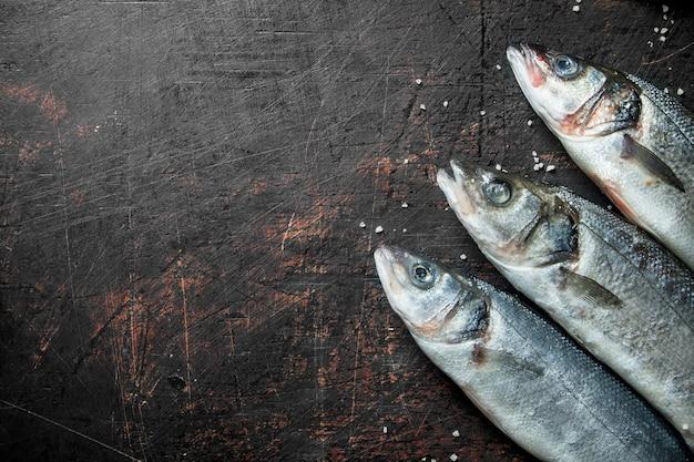 Frischer roher fisch auf rustikalem tisch