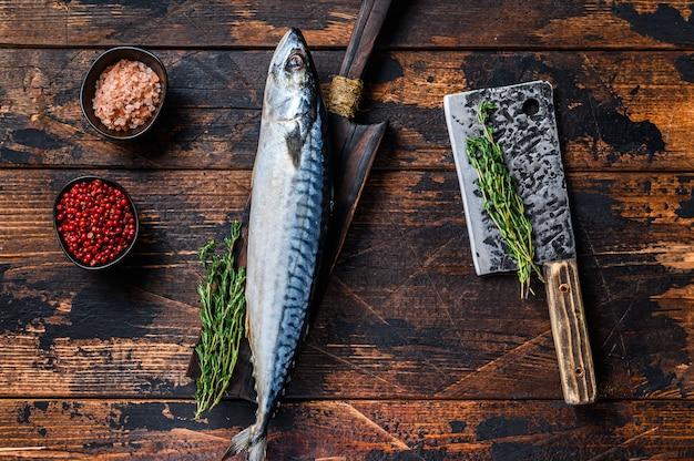 Frischer roher fisch makrele auf einem holzbrett mit einem hackbeil.