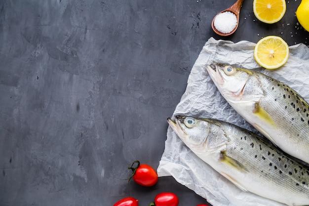 Frischer roher fisch mit gewürzen, zitrone, salz auf dunklem steinhintergrund