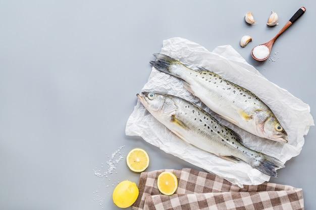 Frischer roher fisch mit gewürzen, zitrone, salz auf grauem hintergrund