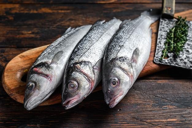 Frischer roher fisch seebarsch auf einem schneidebrett.