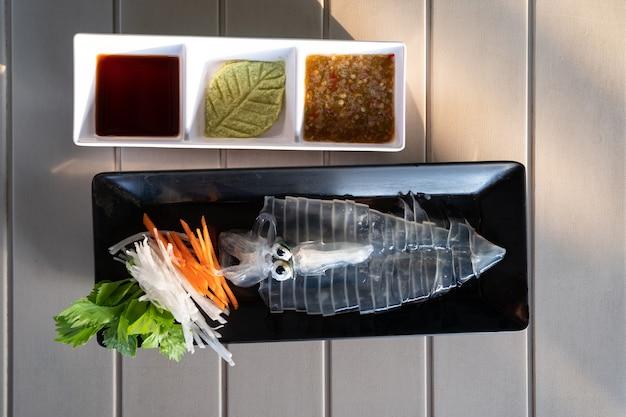 Frischer roher, geschnittener tintenfisch-sashimi auf teller auf weißem holztisch mit meeresfrüchtesauce im thailändischen stil und japanischer sojasauce oder shoyu, super frischer transparenter tintenfisch