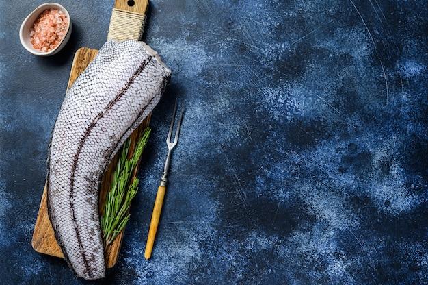Frischer roher grenadier-macrurus-weißfisch auf einem holzbrett. blauer hintergrund.