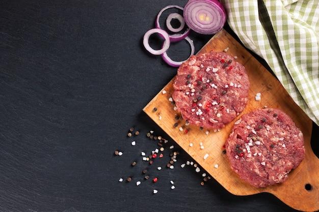 Frischer roher hausgemachter hackfleisch-steak-burger mit gewürzen und zwiebeln auf einem schneidebrett auf einem schwarzen schiefertisch