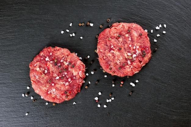 Frischer roher hausgemachter hackfleisch-steak-burger mit gewürzen und zwiebeln, auf einem schwarzen schiefertisch, draufsicht