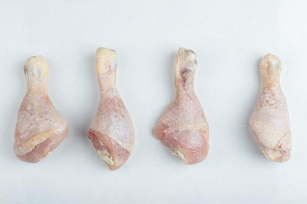 Frischer roher hühnertrommelstock auf weißem hintergrund.