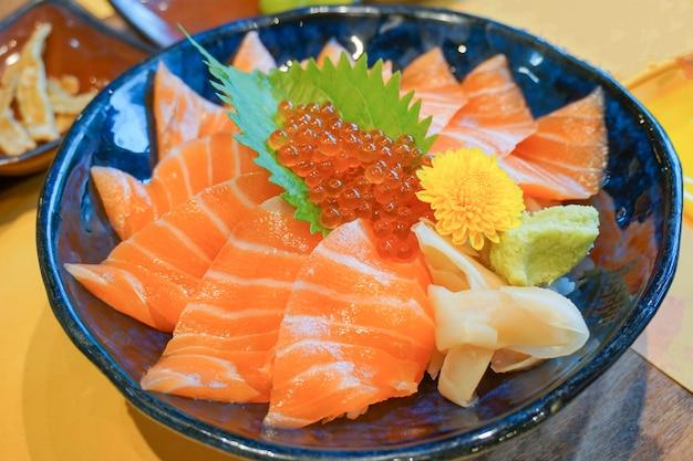 Frischer roher lachs mit lachseiern oder ikura und wasabi auf überzogener reisschale (donburi) - japanische nahrungsmittelart
