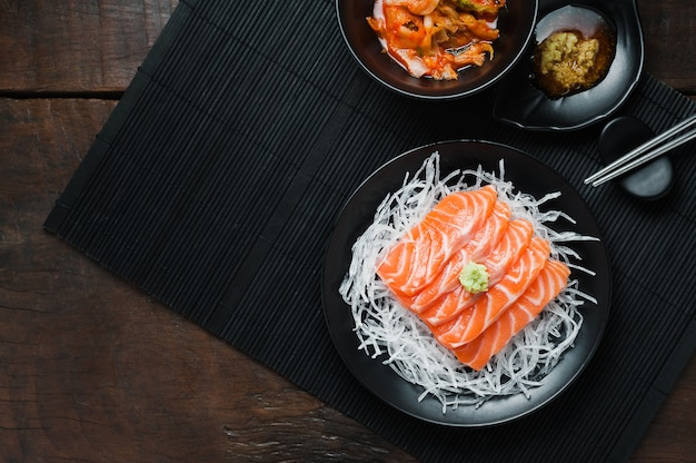Frischer roher lachssashimi auf weiß zerriss rettich in der japanischen art auf holztisch.