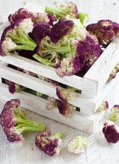 Frischer roher lila blumenkohl auf einem holzbrett hautnah
