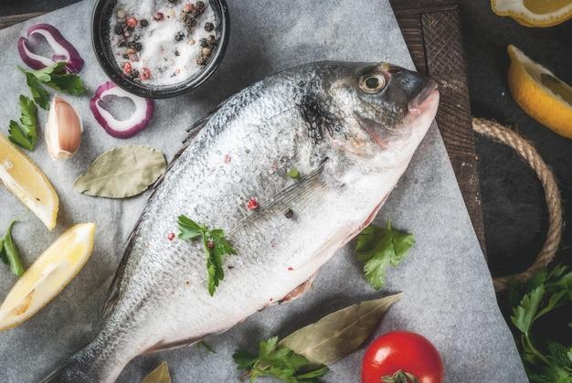 Frischer roher organischer fisch dorado, dorade mit bestandteilen für das kochen der zitrone, der tomaten, der zwiebel, des salzes, des pfeffers, des lorbeers, der grüns, des öls. auf altem hölzernem schneidebrett auf schwarzem steintischplatteansicht-kopienraum