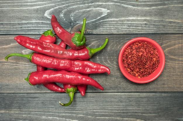 Frischer roher pfeffer der roten paprikas, trockenes gewürz auf hölzerner hintergrundebenenlage