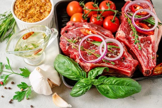 Frischer roher rindfleischknochen mit senfkörnern, würzigem öl, kräutern und gemüse auf grauer betonoberfläche